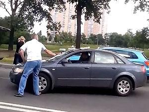 мужчина рубит топором автомобиль