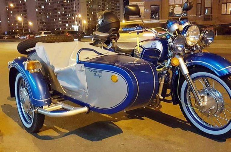 Оказывается, мотоциклы Днепр до сих пор выпускают малыми партиями, хотя и не на Киевском мотозаводе. Но теперь в истории легендарного мотоцикла поставят точку и выпустят ограниченную финальную серию Dnepr Vintage. Dnepr Vintage отличаются особым дизайном и яркой двухцветной окраской (предложены на выбор несколько цветовых схем). Также, мотоциклы с коляской получили дуги, лебедку, дополнительные фары и диодный фонарь. Новый Днепр Винтаж также оснастили вольтметром и датчиком давления масла, а панель приборов получила современную подсветку. Мотоцикл Днепр оснащен 650-кубовым мотором мощностью 32 л. с. Также предусмотрены электростартер и электронная система зажигания с режимами «Нормал», «Спорт» и «Бездорожье». Кроме того, установлены мощный 700-ваттный генератор и более производительная масляная система. Dnepr Vintage представят в рамках автофестиваля Old Car Land. Все мотоциклы собраны вручную профессиональными мастерами. Цена Днепр Винтаж пока не названа.